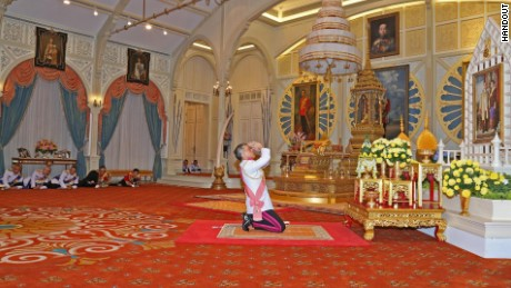 Vajiralongkorn kneels before a portrait of his parents after being confirmed as King.