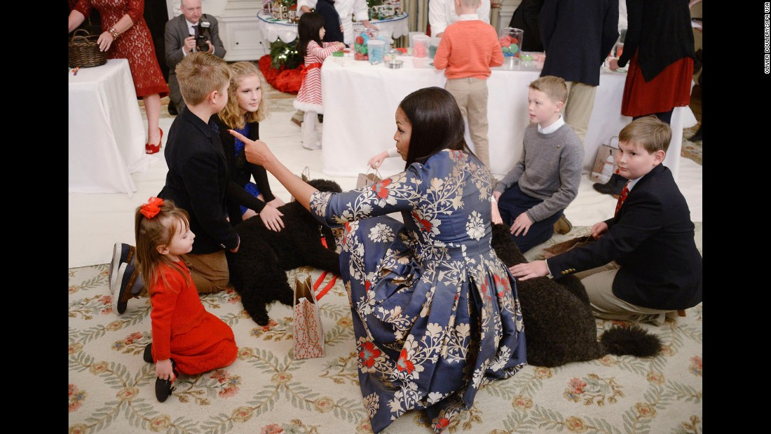 First Lady Michelle Obama, with the First Family's dogs Sunny and Bo, greets children of military families at the unveiling of the 2016 White House holiday decorations in the State Dining Room on November 29.
