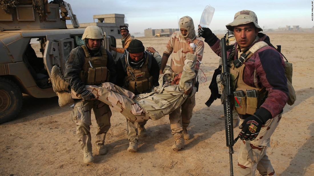 Iraqi soldiers transport a comrade who was injured during a battle near the village of Haj Ali on Tuesday, November 29.