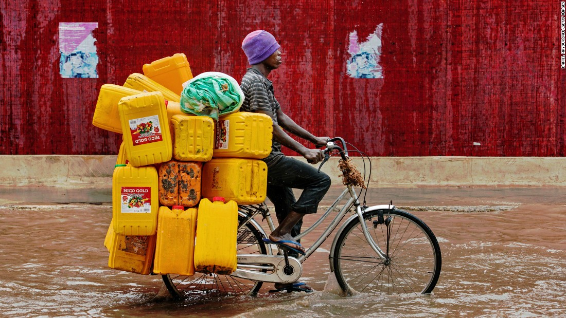 A man bikes down a flooded street with empty cooking oil containers during a storm in Dar es Salaam, Tanzania, on November 23.