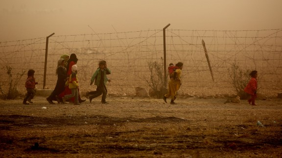 TOPSHOT - Syrian children walk around the camp grounds during a sandstorm at a temporary refugee camp in the village of Ain Issa, housing people who fled Islamic State group's Syrian stronghold Raqa, some 50 kilometres (30 miles) north of the group's de facto capital on November 10, 2016.The US-backed Syrian Democratic Forces (SDF) said their advance on Raqa was being held back by a sandstorm that had hit the desert province. Speaking in Ain Issa, the main staging point for the operation some 50 kilometres (30 miles) north of Raqa, the commander said the sandstorm was also impeding visibility for coalition warplanes. / AFP / DELIL SOULEIMAN        (Photo credit should read DELIL SOULEIMAN/AFP/Getty Images)