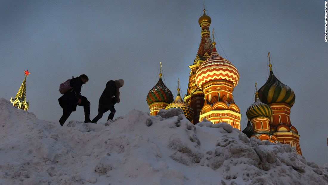 People climb over a snowdrift near St. Basil's Cathedral in Moscow's Red Square after a heavy snowfall on November 12.
