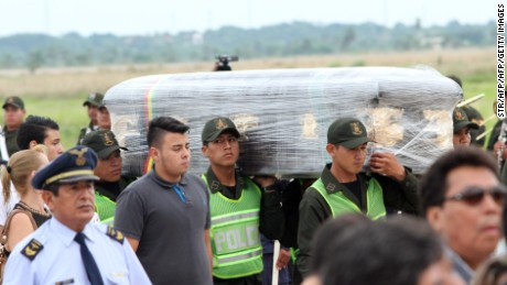 Police and family members receive the coffins sent from Medellin, Colombia with the remains of five Bolivians killed in November 28 plane crash, on December 2, 2016 in Santa Cruz, Bolivia.  The accident claimed 64 Brazilians, five Bolivians and a Venezuelan -- whose bodies were flown home for respective funerals. / AFP / STR        (Photo credit should read STR/AFP/Getty Images)