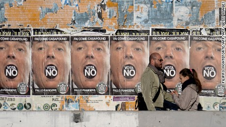"People walk past poster of far-right political movement CasaPound which call to vote ""No"" at the constitutional referendum, on November 30, 2016 in Rome. Italy holds a referendum on December 4, 2016 on proposed constitutional reforms that are considered the most important in the eurozone country since World War II.  / AFP / FILIPPO MONTEFORTE        (Photo credit should read FILIPPO MONTEFORTE/AFP/Getty Images)"