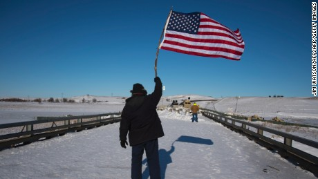 US Navy veteran John Gutekanst from Athens, Ohio, waves an American flag as an activist approaches the police barricade with his hands up on a bridge near Oceti Sakowin Camp on the edge of the Standing Rock Sioux Reservation on December 4, 2016 outside Cannon Ball, North Dakota. Native Americans and activists from around the country gather at the camp trying to halt the construction of the Dakota Access Pipeline.  / AFP / JIM WATSON        (Photo credit should read JIM WATSON/AFP/Getty Images)