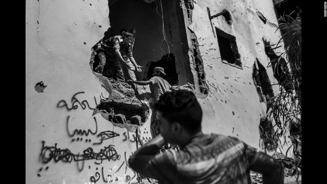 Libyan fighters enter a damaged building.