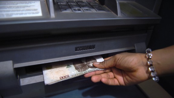 A customer withdraws Nigerian naira from an automated teller machine (ATM) at a bank in Asaba, Delta State.