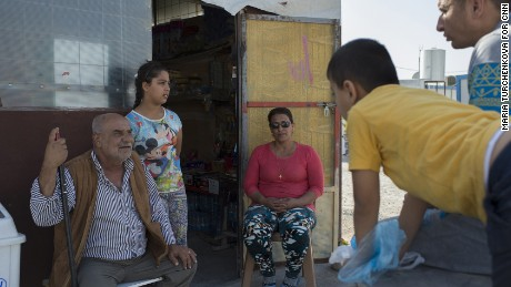 Raja Paulous, center, talks to neighbors at the entrance to her refugee camp grocery.