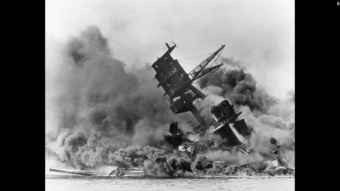 Smoke plumes envelop the USS Arizona battleship as it keels over before sinking in Pearl Harbor.