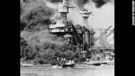 Pearl Harbor, Hawaii. A small boat rescues a seaman from the 31,800 ton USS West Virginia burning in the foreground. Smoke rolling out amidships shows where the most extensive damage occurred. Note the two men in the superstructure. The USS Tennessee is inboard