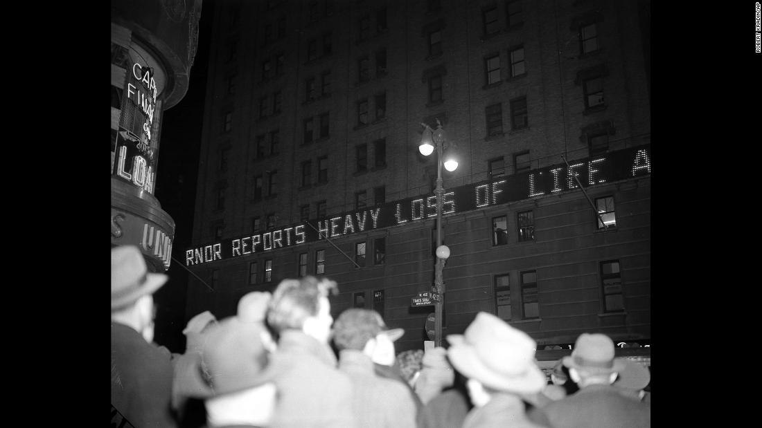 Crowds gather in New York's Times Square as news bulletins flash across the New York Times building announcing the attack on Pearl Harbor.