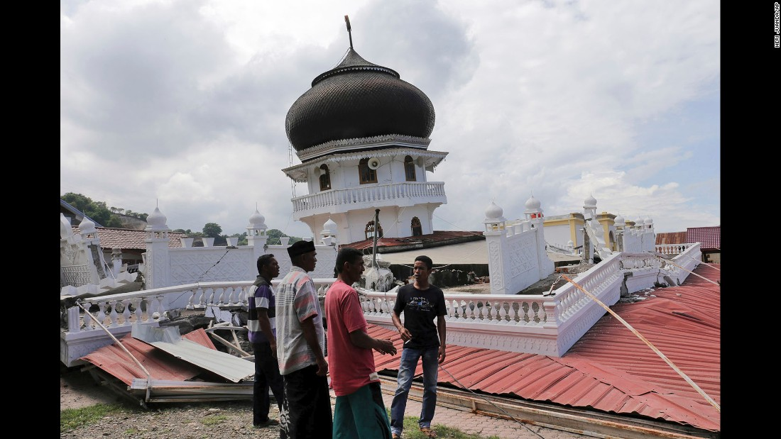 Men inspect a mosque that collapsed during the quake, which struck just as people were preparing for morning prayers on December 7.