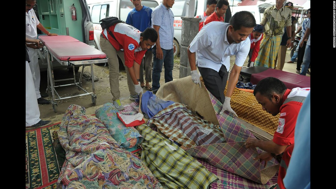 Indonesian Red Cross volunteers cover the bodies of victims at a hospital morgue. Additional medical workers had to be flown in after a local hospital was damaged in the quake.