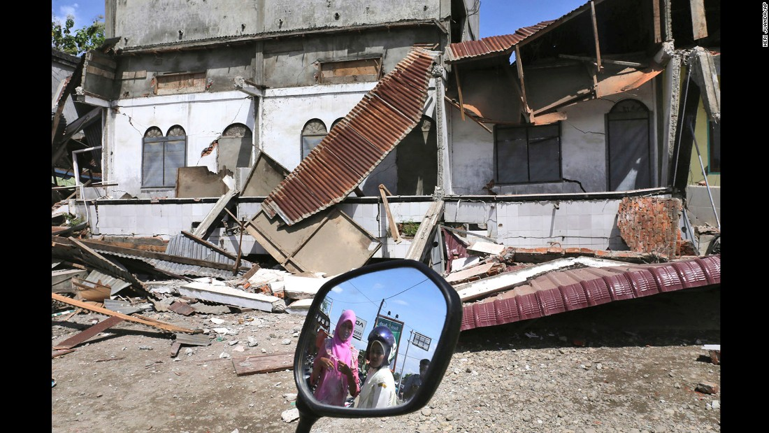 Two women are reflected in the mirror of a motorbike parked near a damaged building in Pidie Jaya.