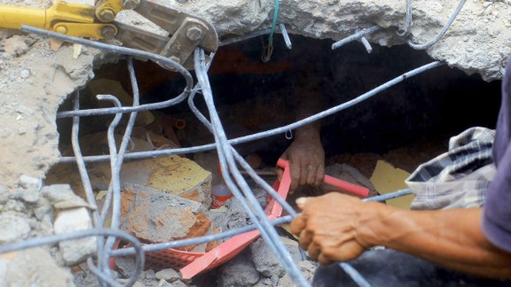 A survivor's hand reaches out from under a collapsed building while rescuers work to free the person.