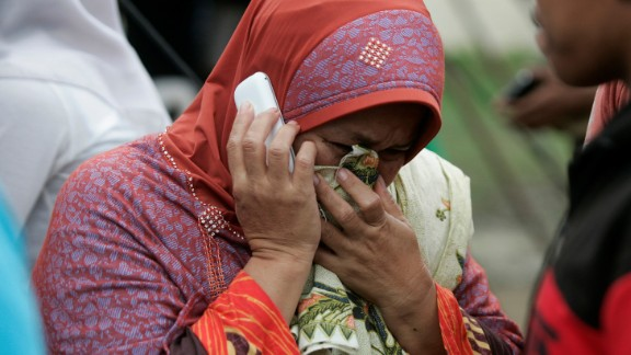 A distraught woman makes a phone call outside a hospital in Pidie Jaya.