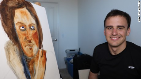 27-year-old Brian Menish, a recovering addict who paints using his left hand.