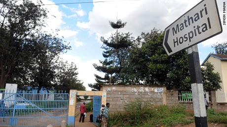 A woman carrying a baby walks past a sign showing the direction to the Mathari hospital on May 13, 2013 in Nairobi.