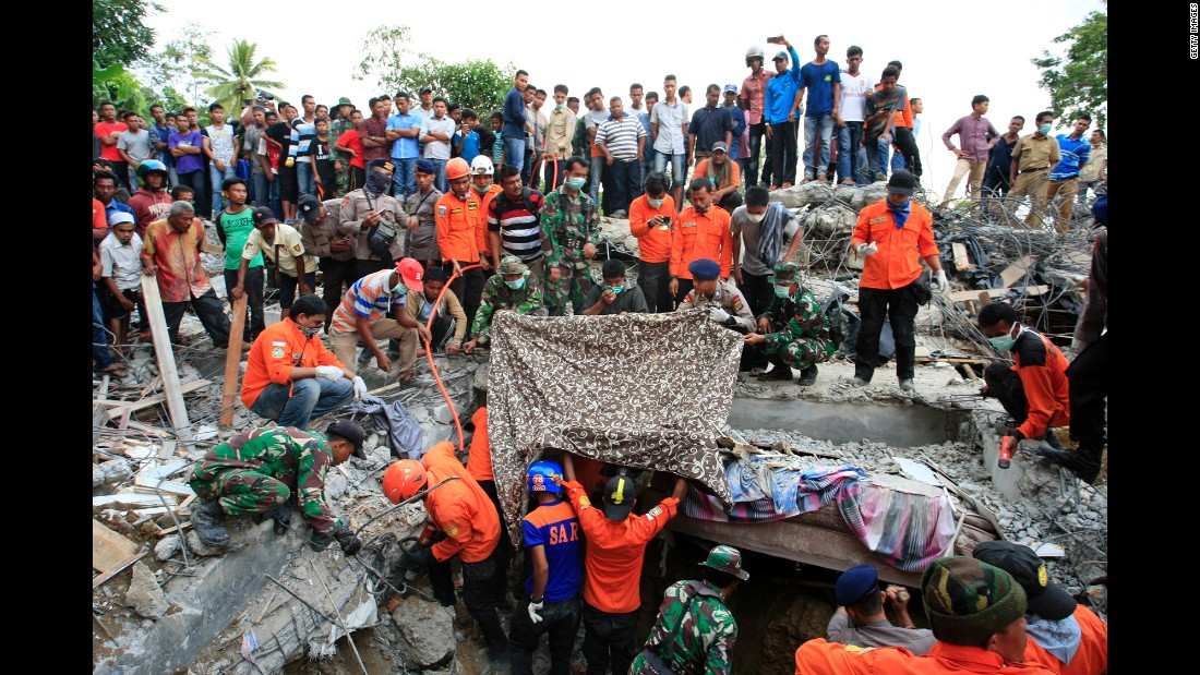 Rescuers, along with members of the Indonesian army, search debris for survivors in Lueng Putu town, Aceh province.