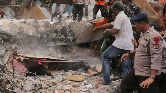 Rescuers work to recover the body of an earthquake victim from a collapsed building. The death toll is expected to rise as rescuers retrieve more victims from under the rubble.
