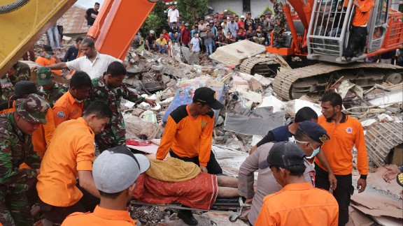 Rescuers recover a body from the rubble of a collapsed building in Pidie Jaya.