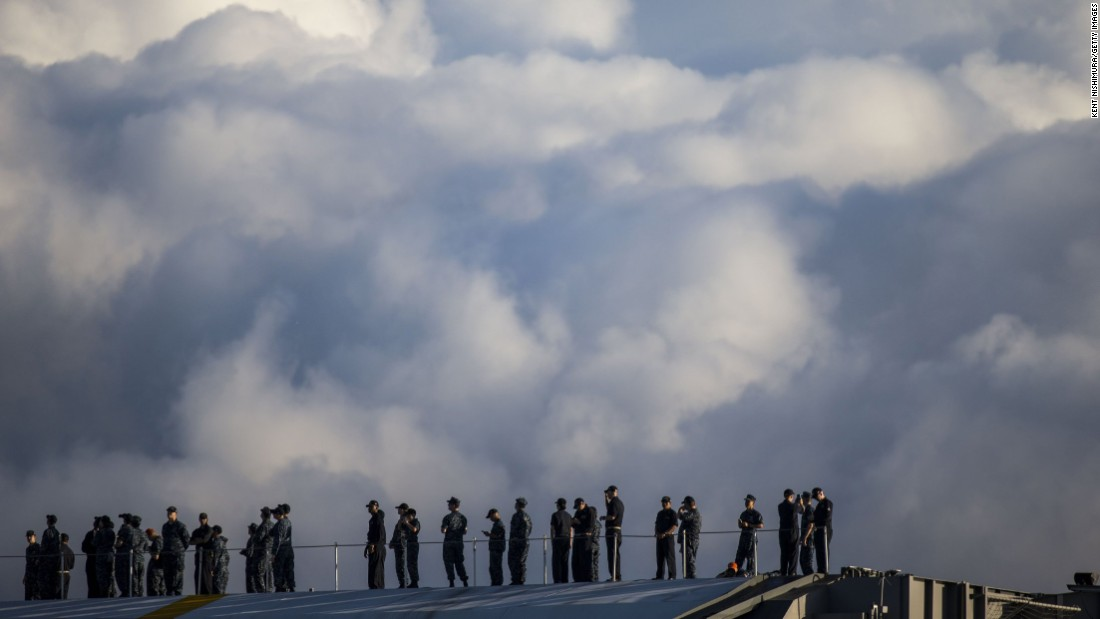 Crew members of the USS John C. Stennis stand on deck of the guided missile destroyer USS Halsey in Honolulu.