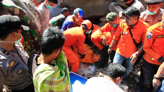 Rescue workers pull victims from destroyed buildings  Wednesday in the town of Sigli.