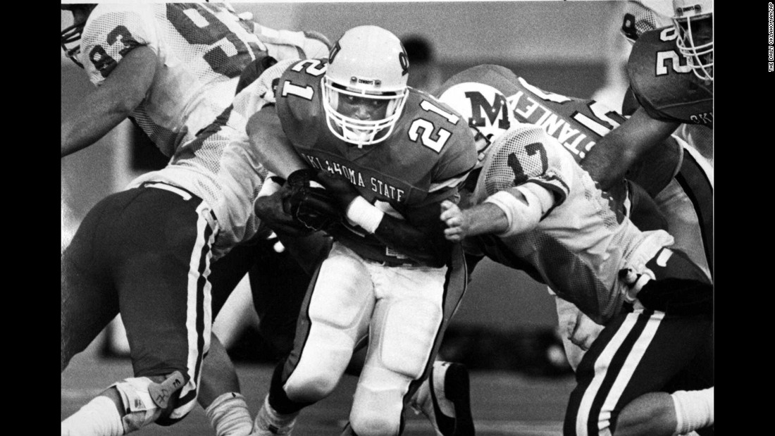 Barry Sanders, playing for Oklahoma State, pushes his way through Miami University-Oxford players during a game in Stillwater, Oklahoma, on September 10, 1988.