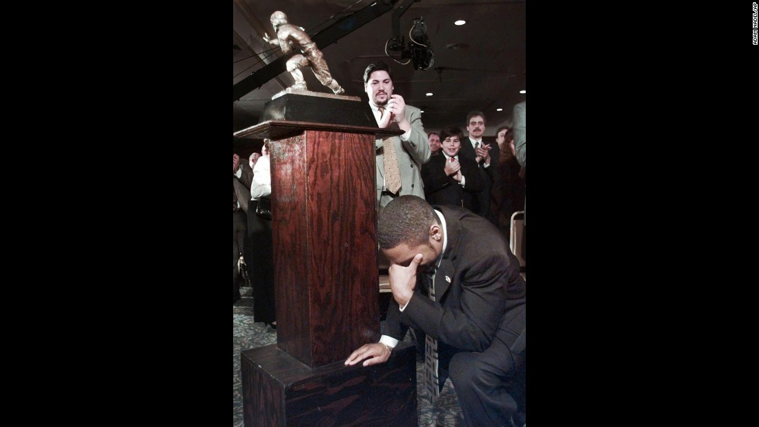 Michigan's Charles Woodson kneels beside the Heisman Trophy after becoming the first primarily defensive player to win the honor at the Downtown Athletic Club in New York on December 13, 1997.