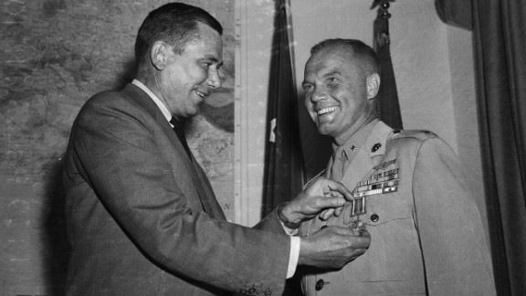 Glenn receives a Distinguished Flying Cross from then-Navy Secretary Thomas Gates at the Pentagon.