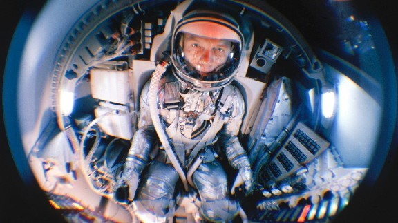 Glenn, now a Project Mercury astronaut, is seen through fisheye lens during training in a mock-up of a space capsule.
