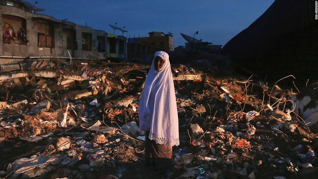 A woman stands amid the rubble of a market that was destroyed in the quake in Meureudu, on December 8.