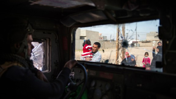 TOPSHOT - People fleeing the fighting are seen from inside an Iraqi Special Forces 2nd division Humvee in Mosul