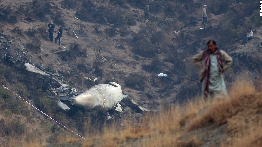 "A villager stands near the site of a plane crash as investigators inspect the scene in the village of Gug, Pakistan, on Thursday, December 8. A Pakistan International Airlines flight <a href=""http://www.cnn.com/2016/12/07/asia/pakistan-missing-plane/index.html"" target=""_blank"">crashed into the mountains</a> near Abbottabad and Havelian, killing all 47 people on board."