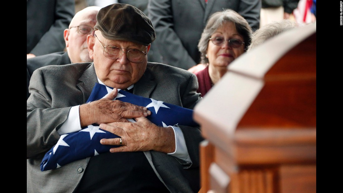 Frank Springs hugs the US flag that draped the casket of his uncle, Jim H. Johnston, a Navy Fireman 1st Class, who was buried with full military honors in Wesson, Mississippi, on Wednesday, December 7.