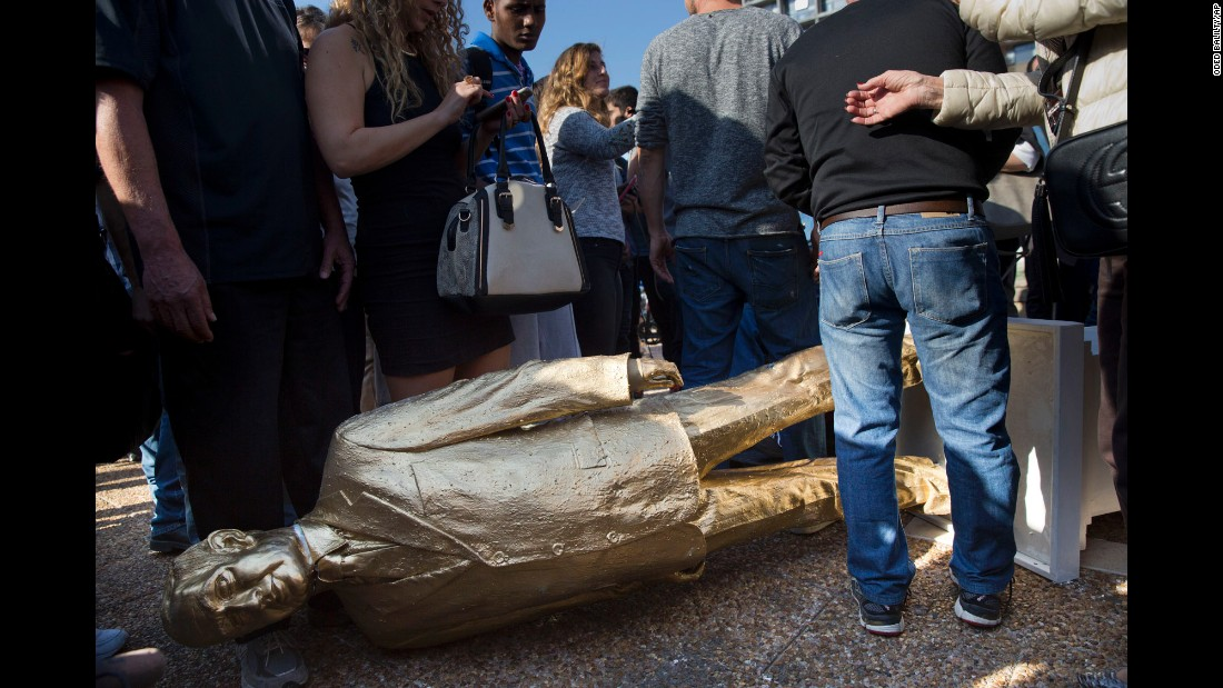 "People stand by a statue of Israeli Prime Minister Benjamin Netanyahu after it was placed at Rabin Square in Tel Aviv, Israel, on Tuesday, December 6. The golden statue -- <a href=""http://www.cnn.com/2016/12/06/middleeast/benjamin-netanyahu-gold-statue/"" target=""_blank"">dubbed ""King Bibi"" by its creator</a> and as a reference to the biblical golden calf -- is the work of Israeli sculptor Itay Zalait. The sculptor said he placed the statue there because he wanted to make people think about freedom of expression in the country. Zalait was later ticketed and fined by the municipal council."