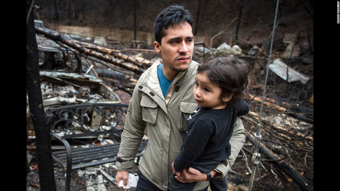 "Allan Rivera holds his son, Nathan Rivera, as he looks at the remains of their home in Gatlinburg, Tennessee, on Monday, December 5. A Tennessee wildfire began on November 27 and spread to 17,000 acres -- including the mountain resort of Gatlinburg -- killing 14 people and injuring 175. <a href=""http://www.cnn.com/2016/12/07/us/gatlingburg-fire-charges/index.html"" target=""_blank"">Two juveniles are facing charges of aggravated arson</a> in connection with the wildfire, according to authorities. <a href=""http://www.cnn.com/2016/12/02/us/gatlinburg-fire-pictures-before-after/index.html"" target=""_blank"">Gatlinburg before and after the fire</a>"