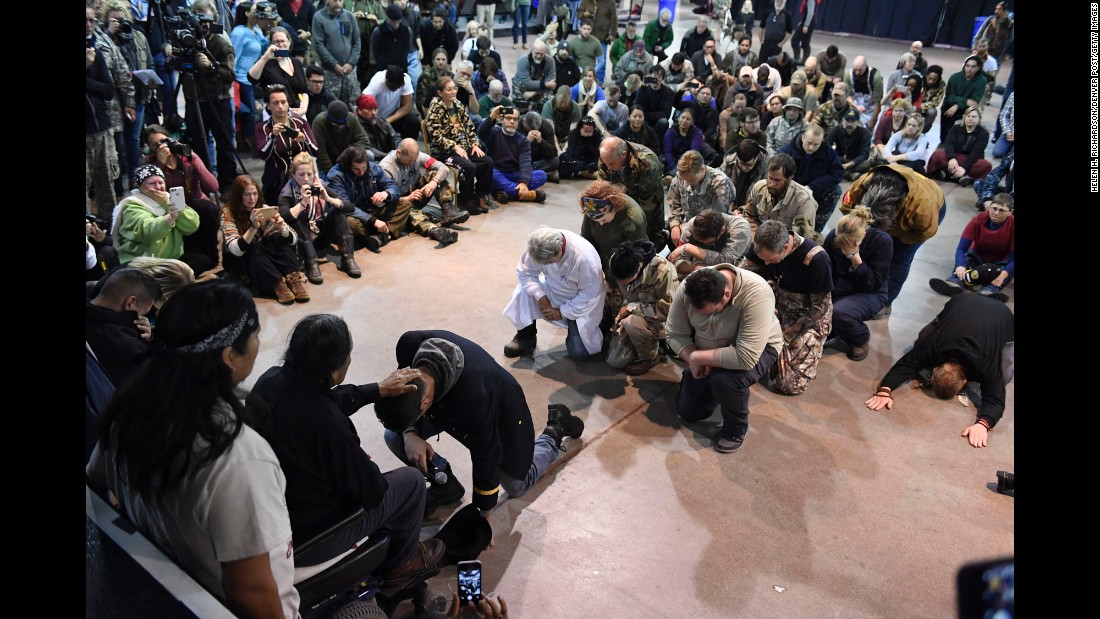 Wesley Clark Jr. kneels in front of Leonard Crow Dog during a forgiveness ceremony at the Standing Rock Sioux Reservation in Fort Yates, North Dakota, on Monday, December 5. A group of US veterans asked Native Americans to forgive the military actions carried out against the Native American people throughout history.