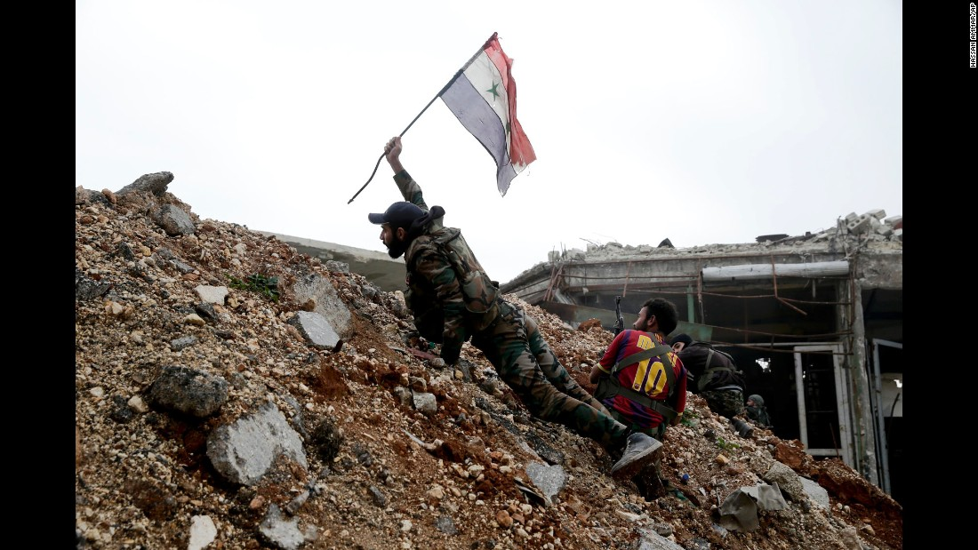 A Syrian Army soldier places a Syrian flag in the ground during a battle with rebel fighters in Aleppo, Syria, on Monday, December 5.