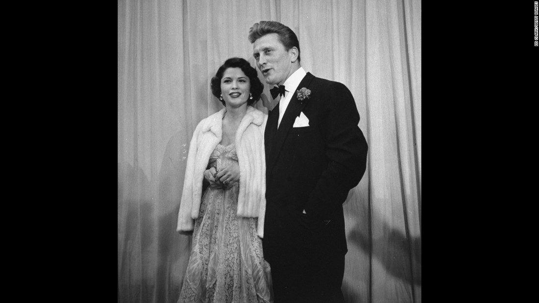 "Douglas escorts Irene Wrightsman McEvoy to the Academy Awards in March 1950.  He was nominated that year for best actor for his breakout role in ""Champion."" He would also be nominated for ""The Bad and the Beautiful"" and ""Lust for Life."" The star received an honorary Academy Award in 1996."