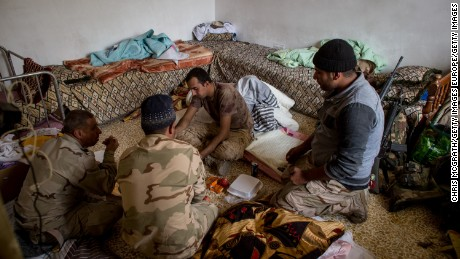 Iraqi soldiers eat in a house  in the Entisar neighborhood of Mosul last month.