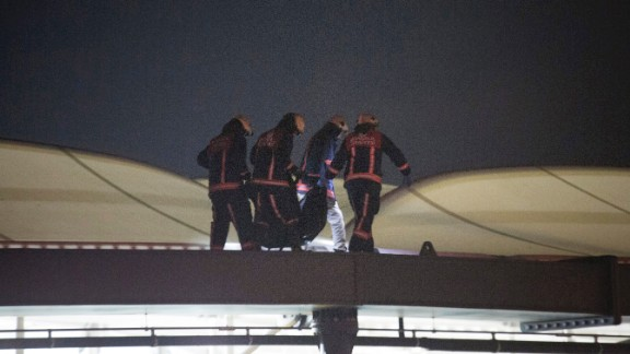 Firefighters carry a dead body through the roof of the stadium at the scene of the explosions.