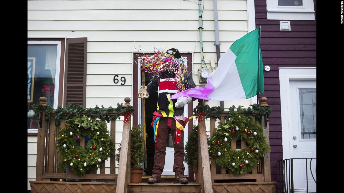 "Wally Upward stands on his home's porch while dressed as a ""ribbon fool."""