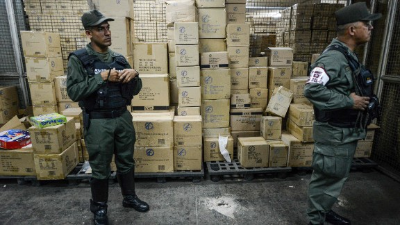 Members of the Venezuelan national guard stand next to boxes full of confiscated toys in a warehouse in Caracas on December 9, 2016. The Venezuelan government seized 3.8 million toys on December 9, 2016 from one of the country