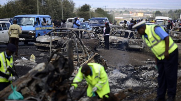 Kenyan police officers search for victims at the crash site.