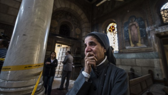 A nun reacts as Egyptian security forces (unseen) inspect the scene of a bomb explosion at the Saint Peter and Saint Paul Coptic Orthodox Church on December 11, 2016, in Cairo