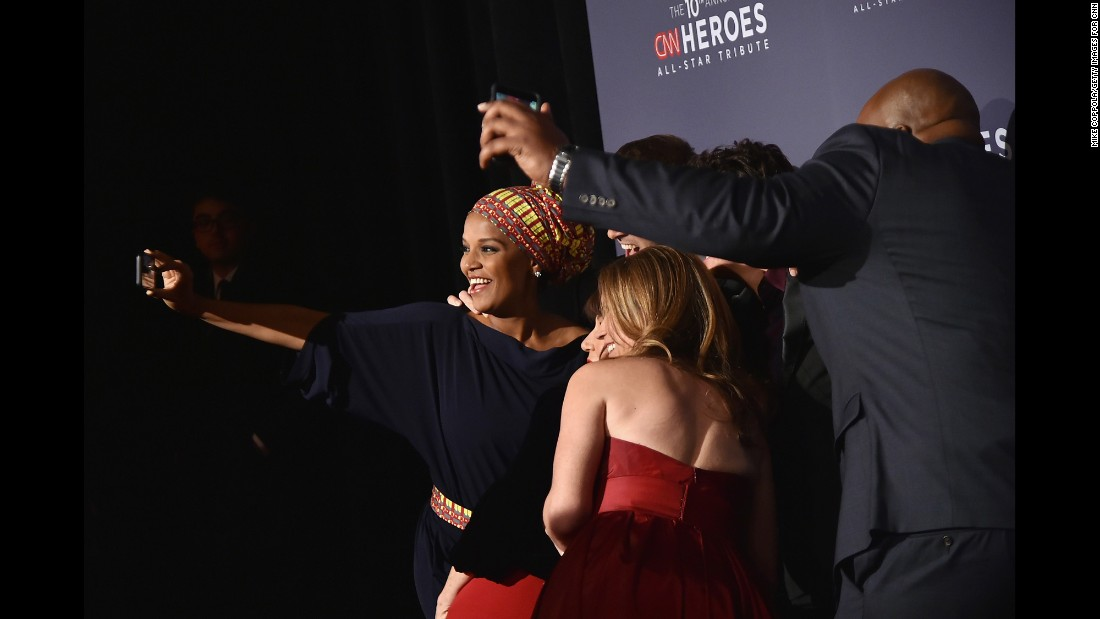 Umra Omar, left, takes a selfie with her fellow Top 10 CNN Heroes on the red carpet as they get ready for the awards show.