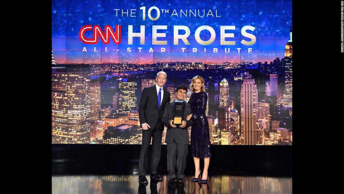 2016 CNN Hero of the Year Jeison Aristizábal poses on stage with hosts Anderson Cooper and Kelly Ripa.