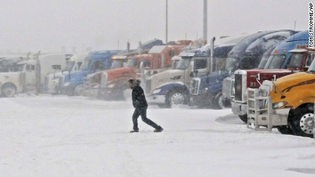 "Alf Carlson, a storm stranded driver from Winnipeg, Manitoba, Canada, walks from his truck to the Stamart Truck Stop in Bismarck, N.D., before dawn on Tuesday, Dec. 6, 2016.. Carlson said he spent the night in his truck waiting out a winter blizzard that forced closure of Interstate 94. ""I'm trying to get to Lame Deer, Montana,"" said Carlson who said he had no choice but wait out the blizzard that forced closures throughout North Dakota. The National Weather Service issued a blizzard warning for much of western and central North Dakota through Tuesday afternoon. (Tom Stromme/The Bismarck Tribune via AP)"