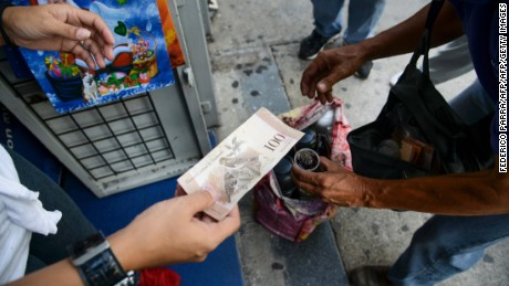 "A woman a coffee to a peddler with a 100-bolivar-bill in Caracas on December 12, 2016. Venezuelan President Nicolas Maduro on Sunday signed an emergency decree ordering the country's largest banknote, the 100 bolivar bill, taken out of circulation to thwart ""mafias"" he accused of hoarding cash in Colombia. / AFP / Federico PARRA        (Photo credit should read FEDERICO PARRA/AFP/Getty Images)"
